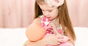 Big sister playing with doll at sibling class